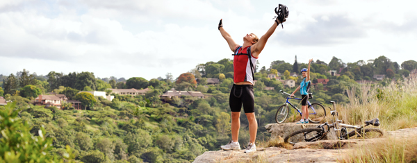 Man celebrates biking in the mountains, with his arms lifted.